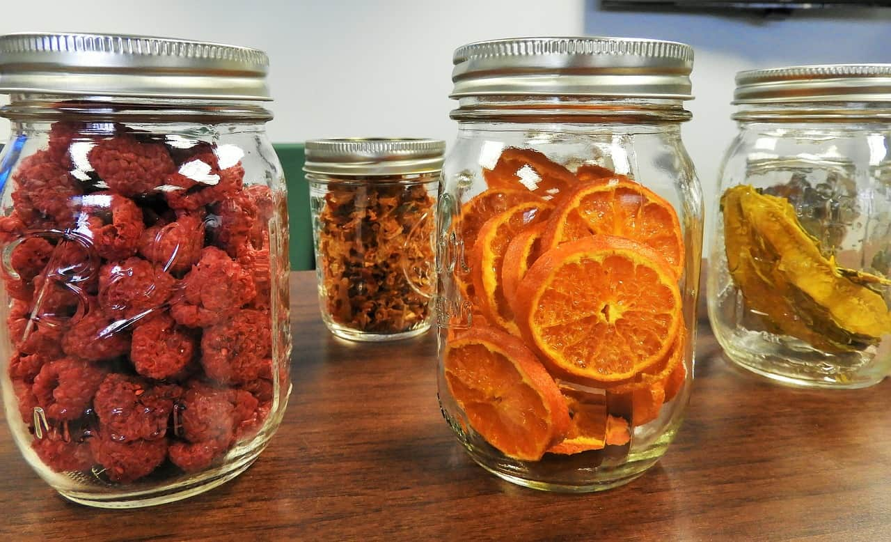 four different freeze dried fruits stored in their respective mason jars