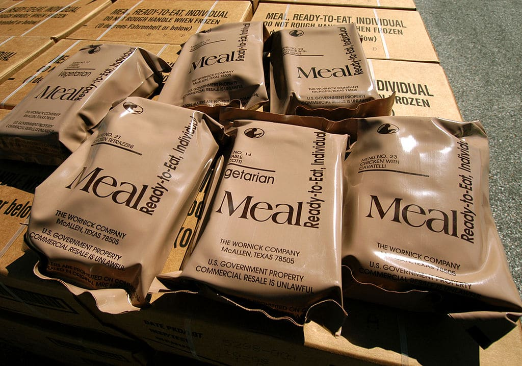 six packs of mres on top of a pile of boxes containing mres