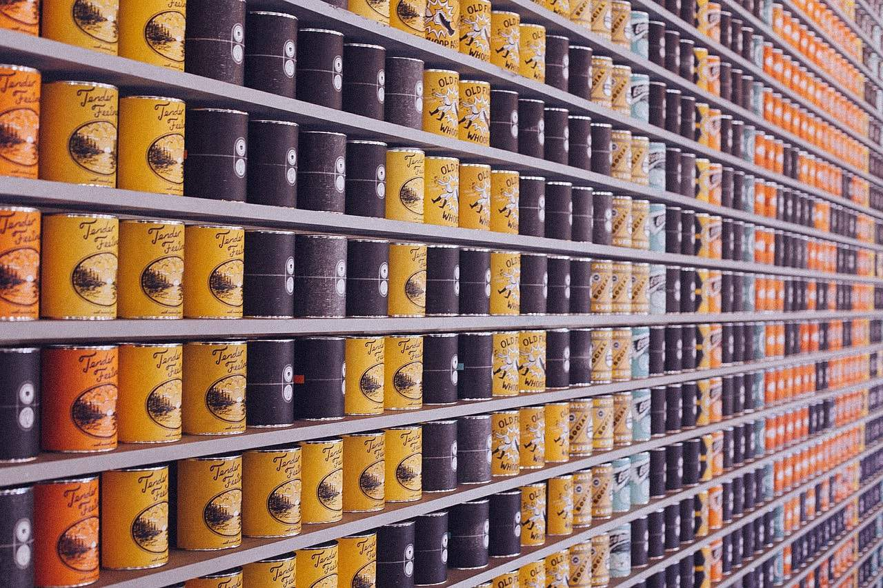shelf of grocery store with shelves full of canned goods