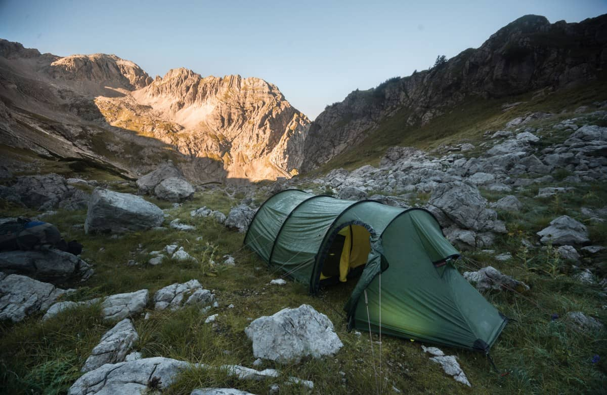 green tube tent put up on a rocky terrain