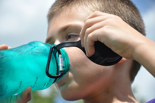 a boy drinking water from a plastic water container