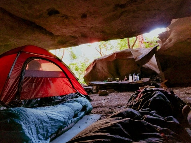 tent and sleeping bag under cave