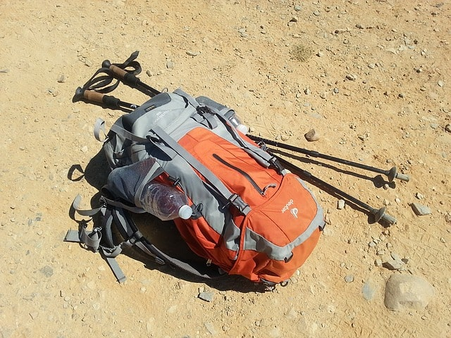 travel backpack and two trekking poles lying on dirt