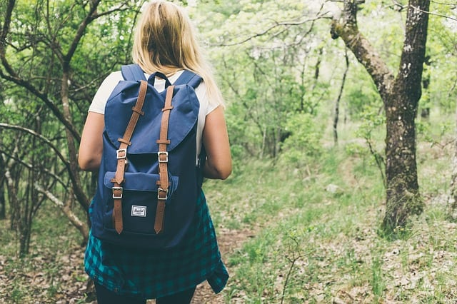 a girl with backpack walking into the woods